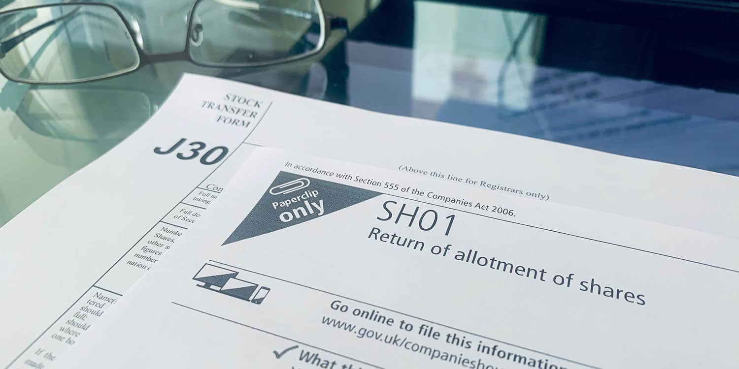 Image of Companies House form SH01, the Return of allotment of shares, and the J30 Stock transfer form lying on a desk. One or both of these forms may be required when you add company shareholders after incorporation.