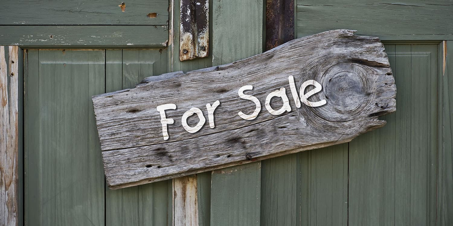 A wooden 'for sale' sign attached to a green door.
