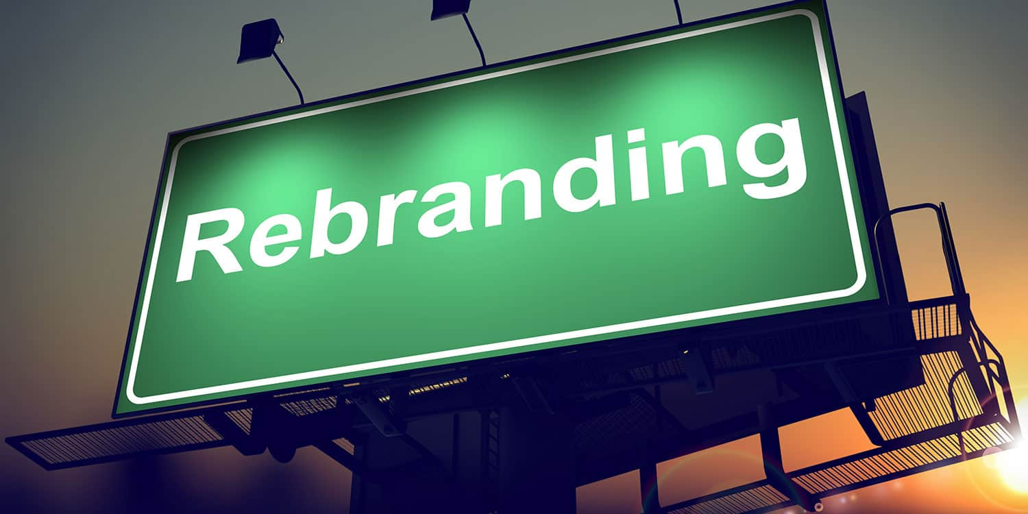 Green illuminated sign displaying the word 'Rebranding' in white letters.