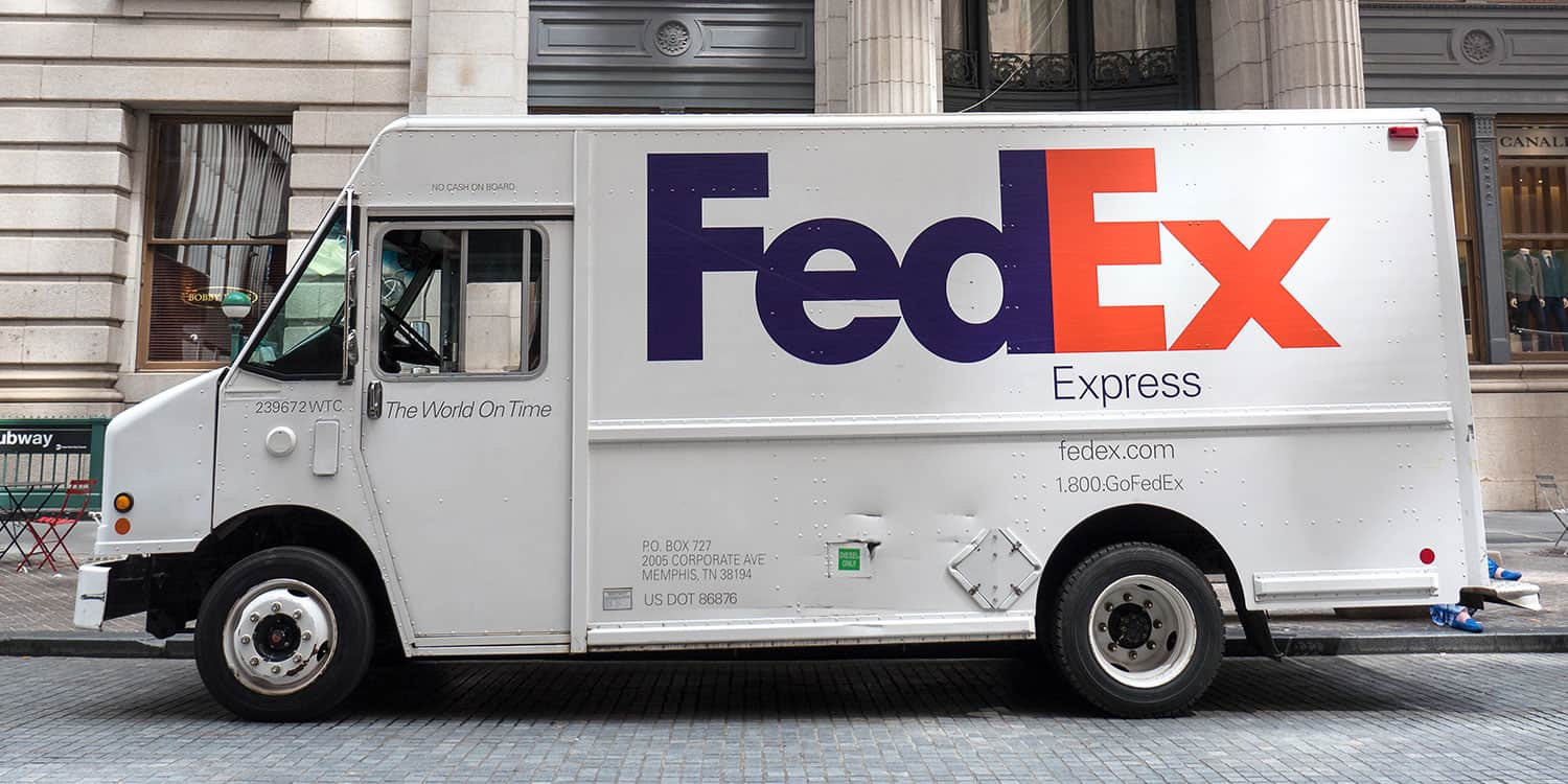 Image of a FedEx van parked outside a building, illustrating the purpose of a business address and shipping address.