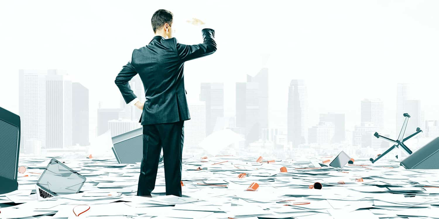Man in a suit surrounded by paper