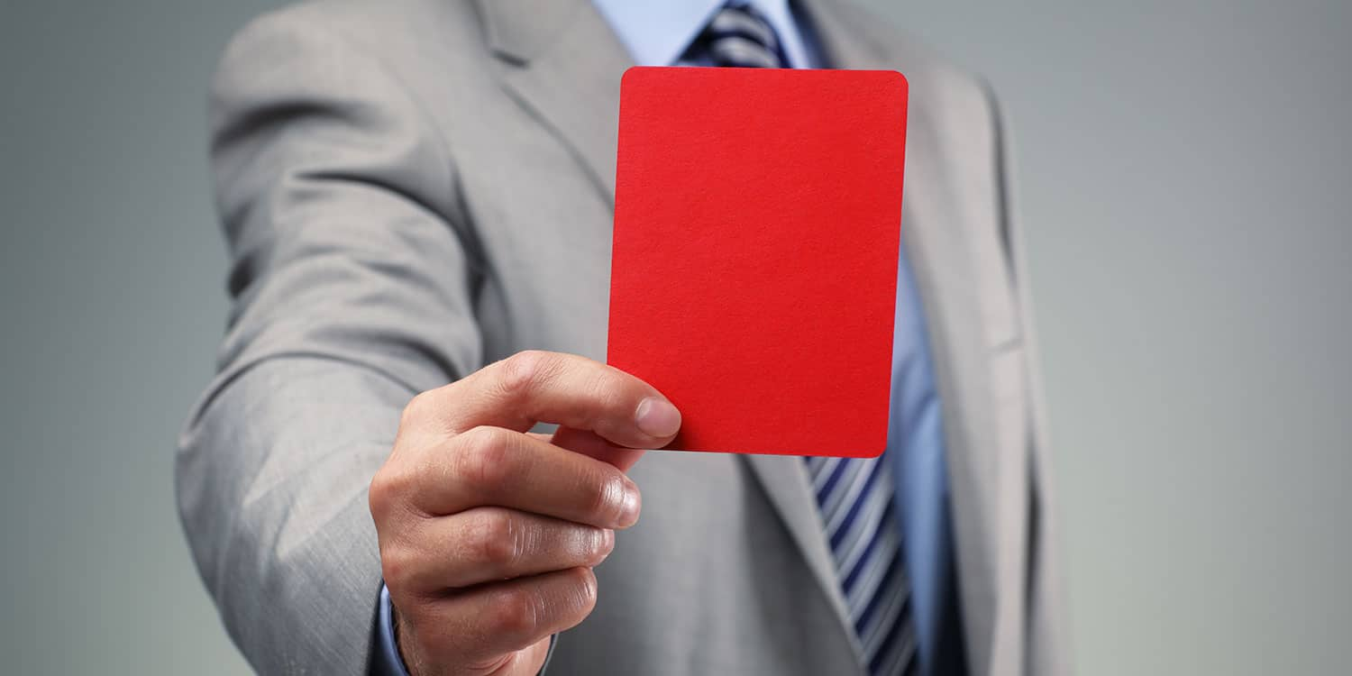 Businessman holing out a red card symbolising director disqualification.