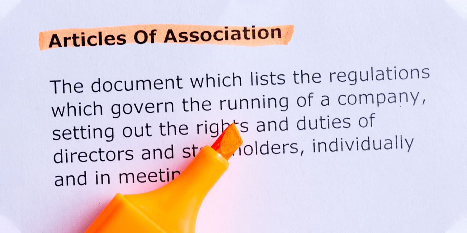 "Orange highlighter on ""Articles of Association"" definition printed on paper."