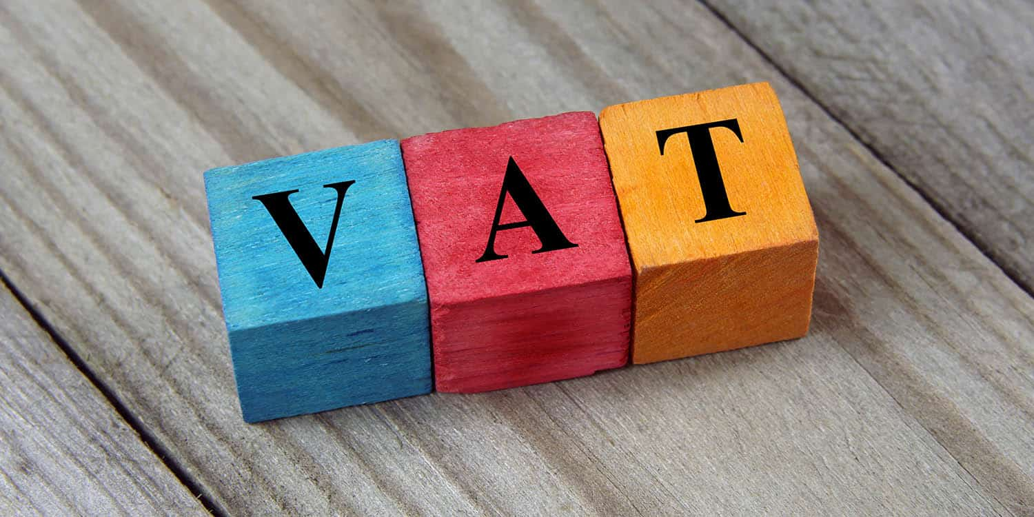 Three coloured wooden blocks, each with a letter in black capitals, spelling the word 'VAT.'