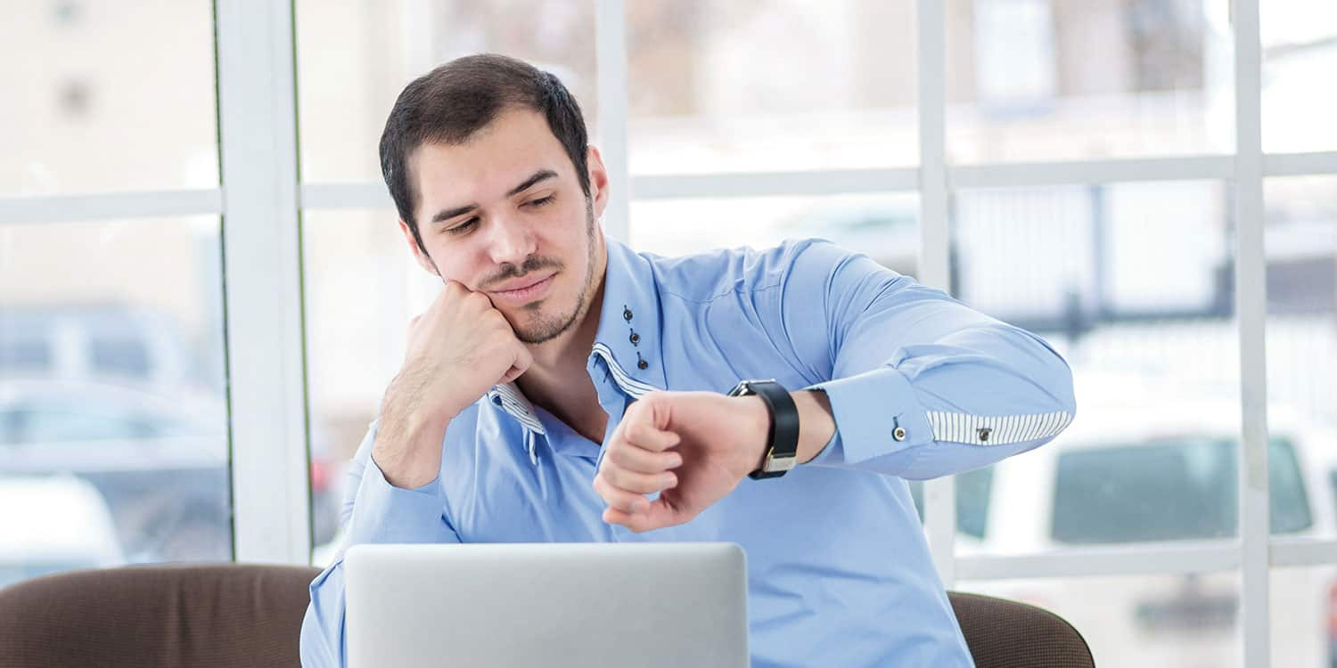 Man in blue shirt, sitting in a modern office, looking at his watch.
