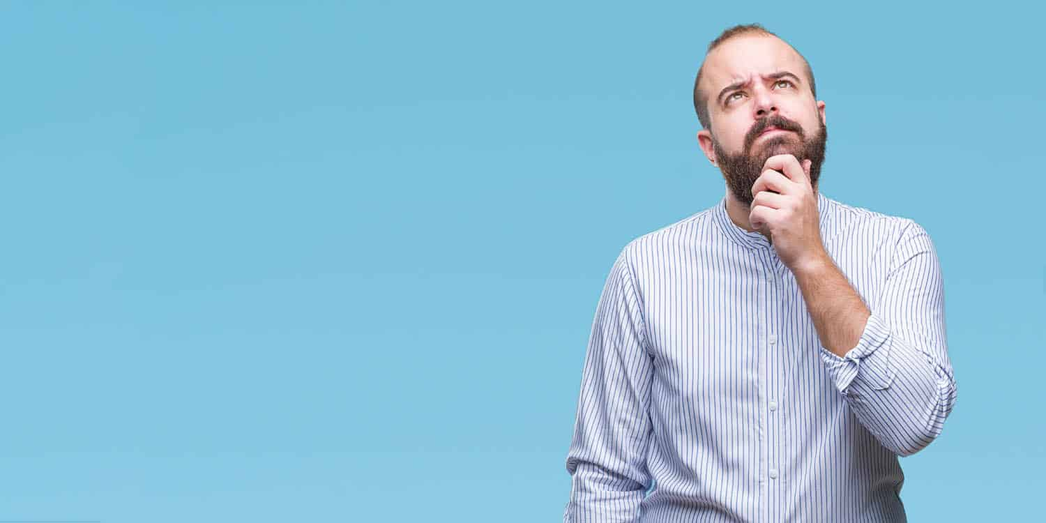 Image of a man with beard and light blue shirt holding his chin and looking upwards in contemplation.