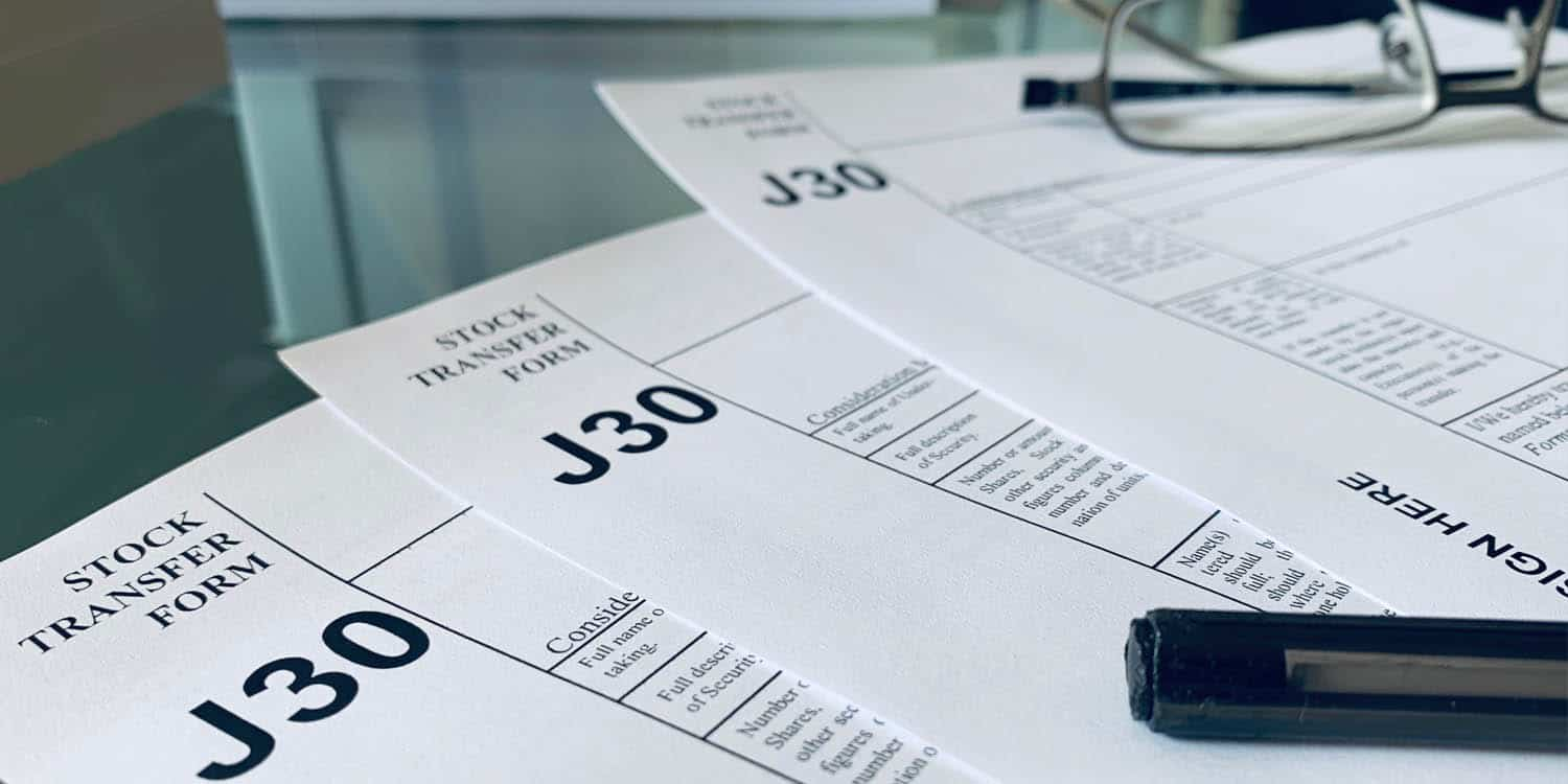 Image of three J30 Stock Transfer Forms placed on top of a glass table.