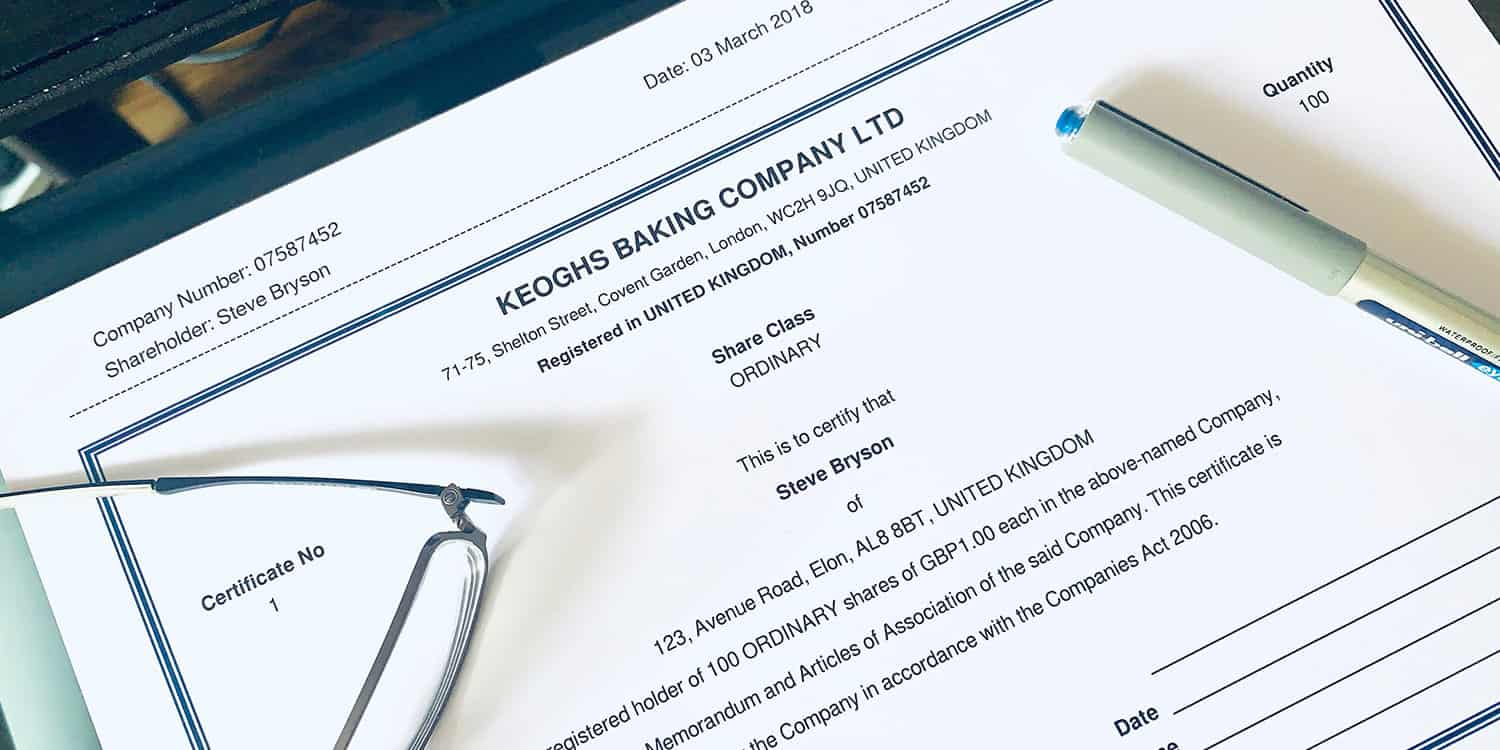 Share certificate on desktop with pen and pair of spectacles - a document you would receive if had shares in a company.