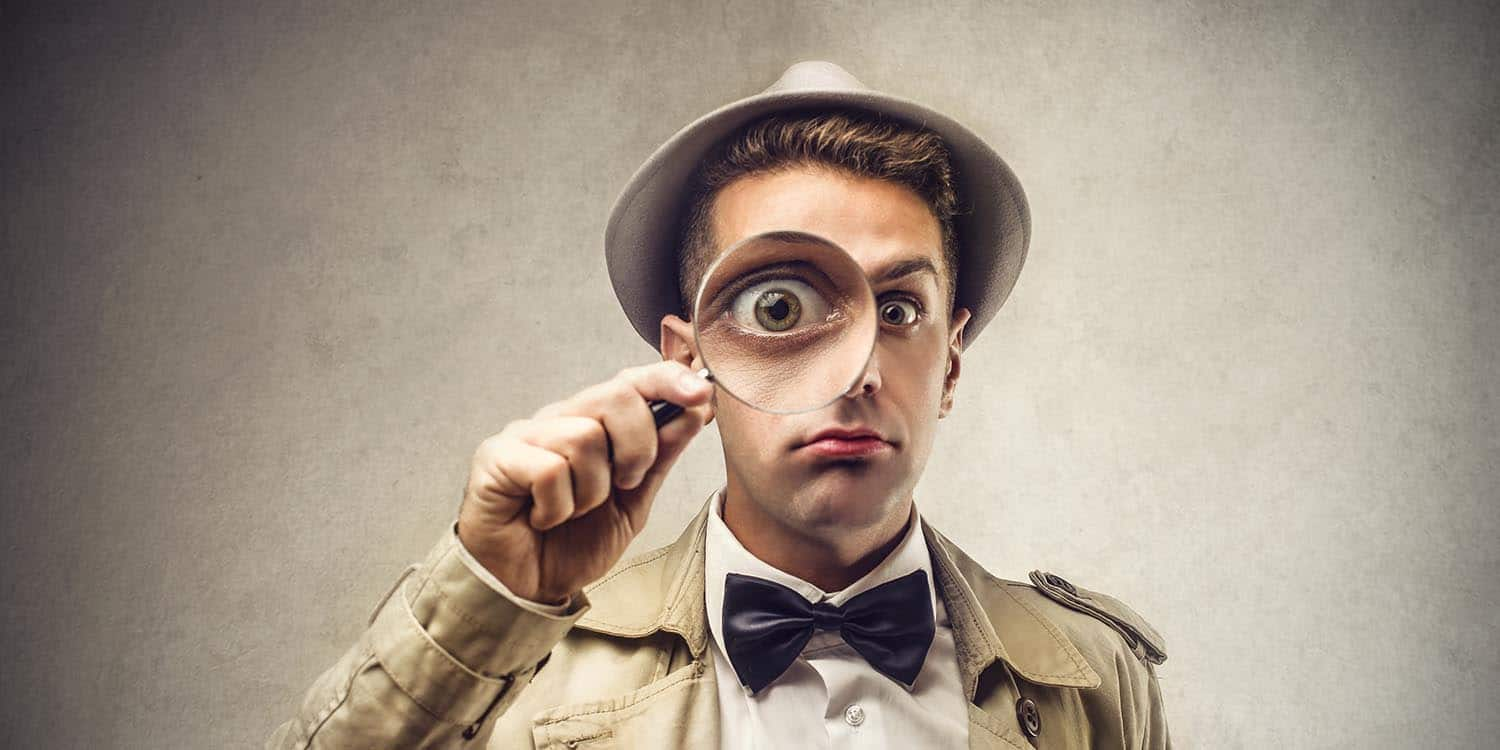 A detective holding a magnifying glass to his eye - symbolising the search for information on a company director.