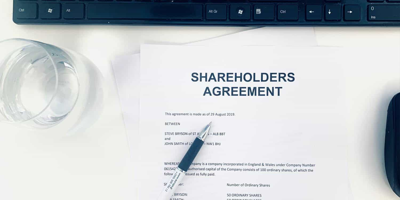 A shareholders' agreement document on a white desk.