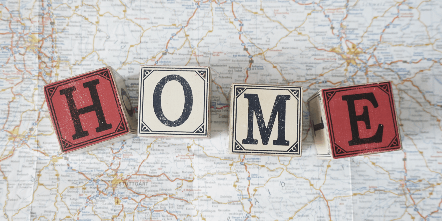 Four wooden blocks each with one letter spelling the word 'HOME' lying on top of a map - symbolising you can use your home address as a registered office?