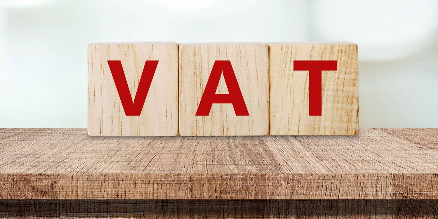 Three wooden blocks spelling out the word 'VAT'.