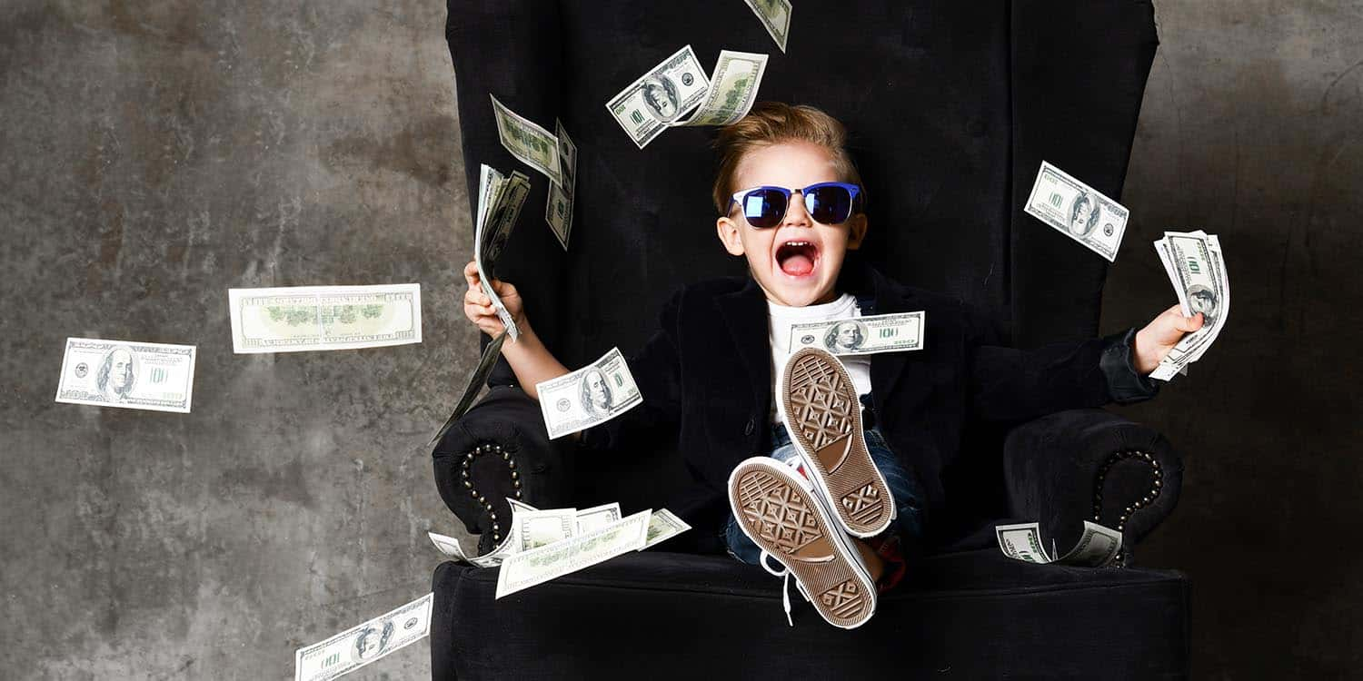 Boy sitting with his feet up on a desk, wearing sunglasses and throwing money in the air.