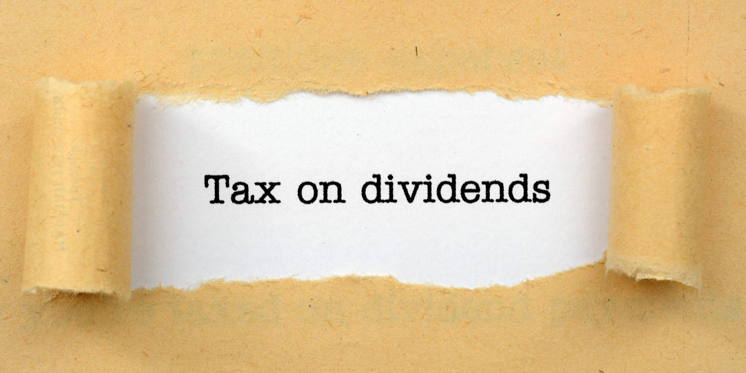 """Image of a brown paper torn open in the middle to reveal the words """"Tax on dividends"""" printed in black ink."""
