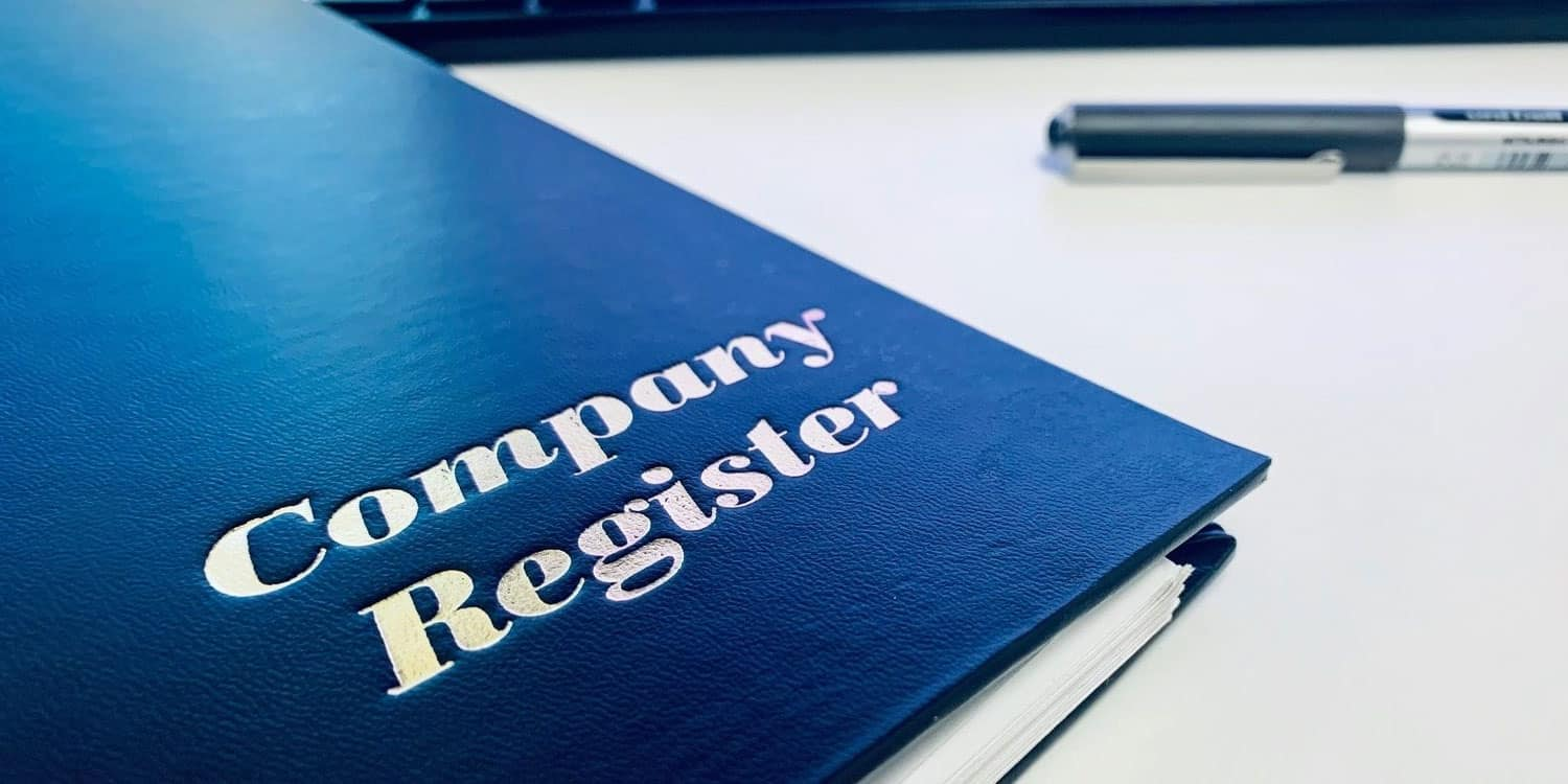 A navy blue ring binder folder titled Company Registers, lying on a desk.