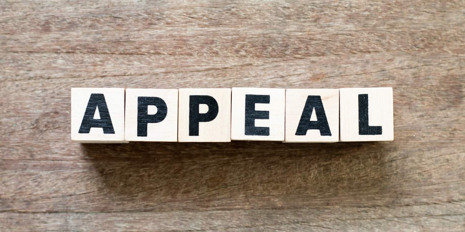 Six wooden blocks, each with a black letter, spelling the word 'APPEAL', illustrating the concept of applying to appeal a filing penalty for late accounts.