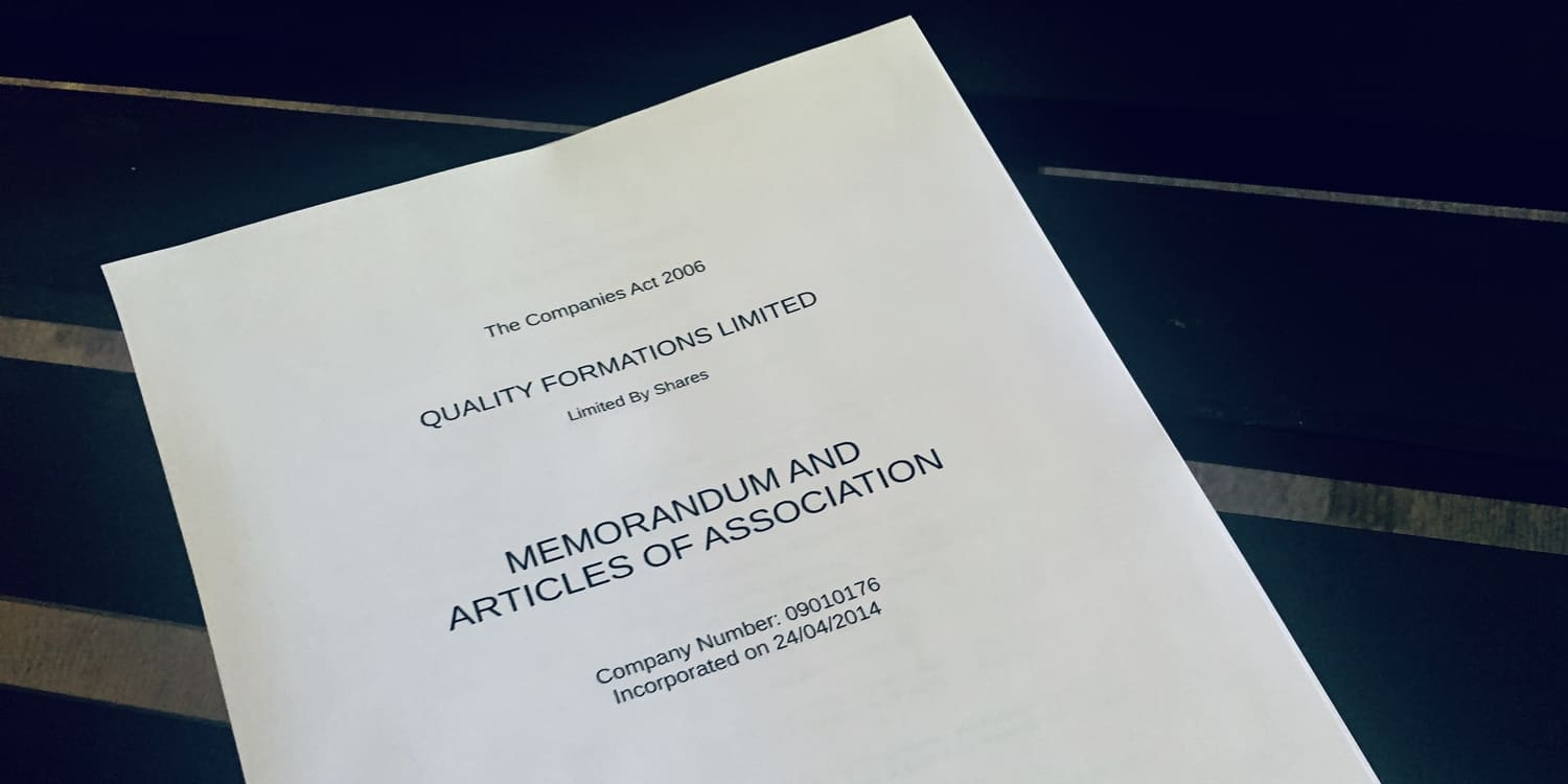Image of a printed copy of articles of association lying n a glass tabletop.