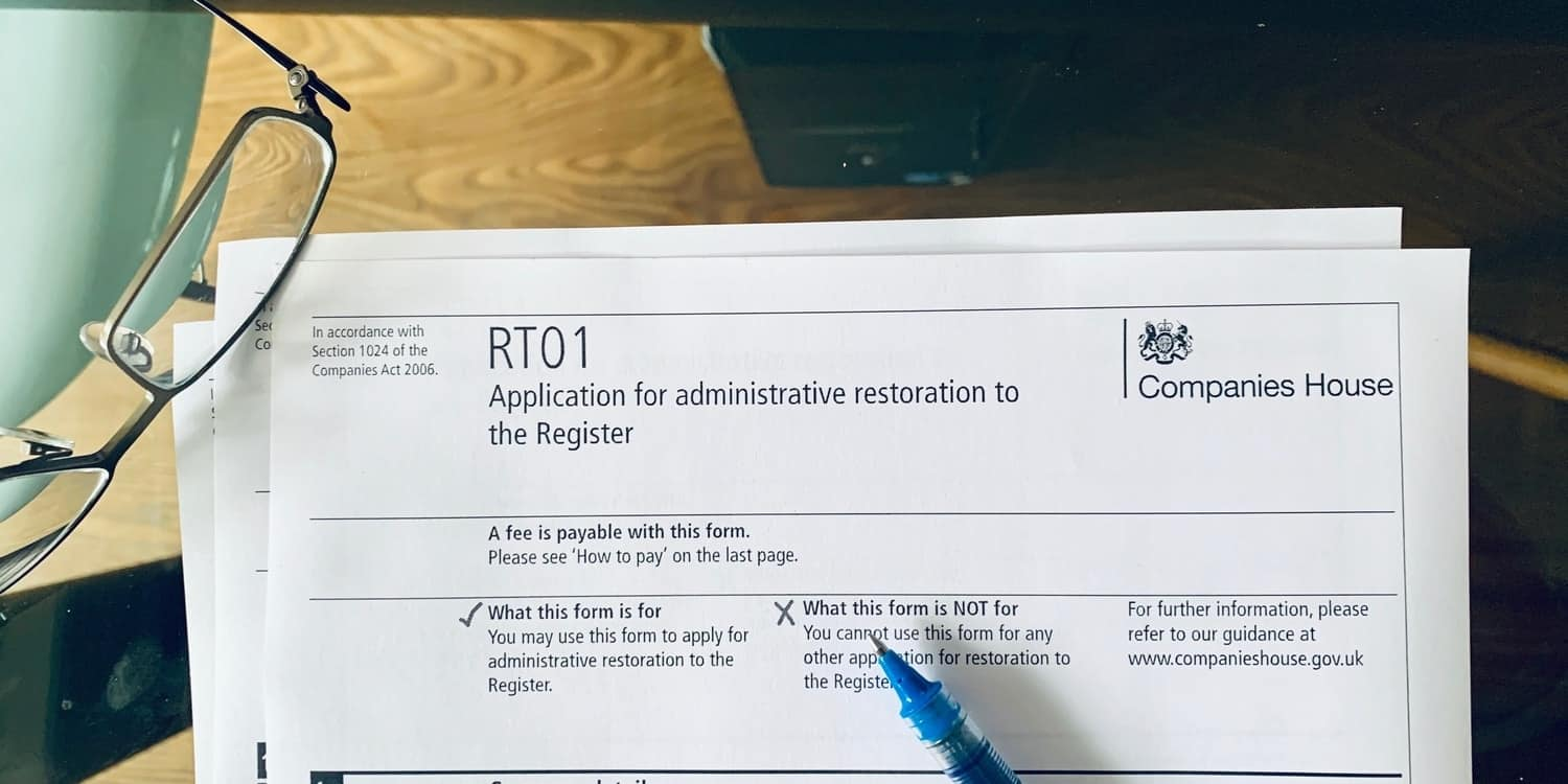 An RT01 form - Application for administrative restoration by the Registrar sitting on a glass desktop with spectacles and pen.