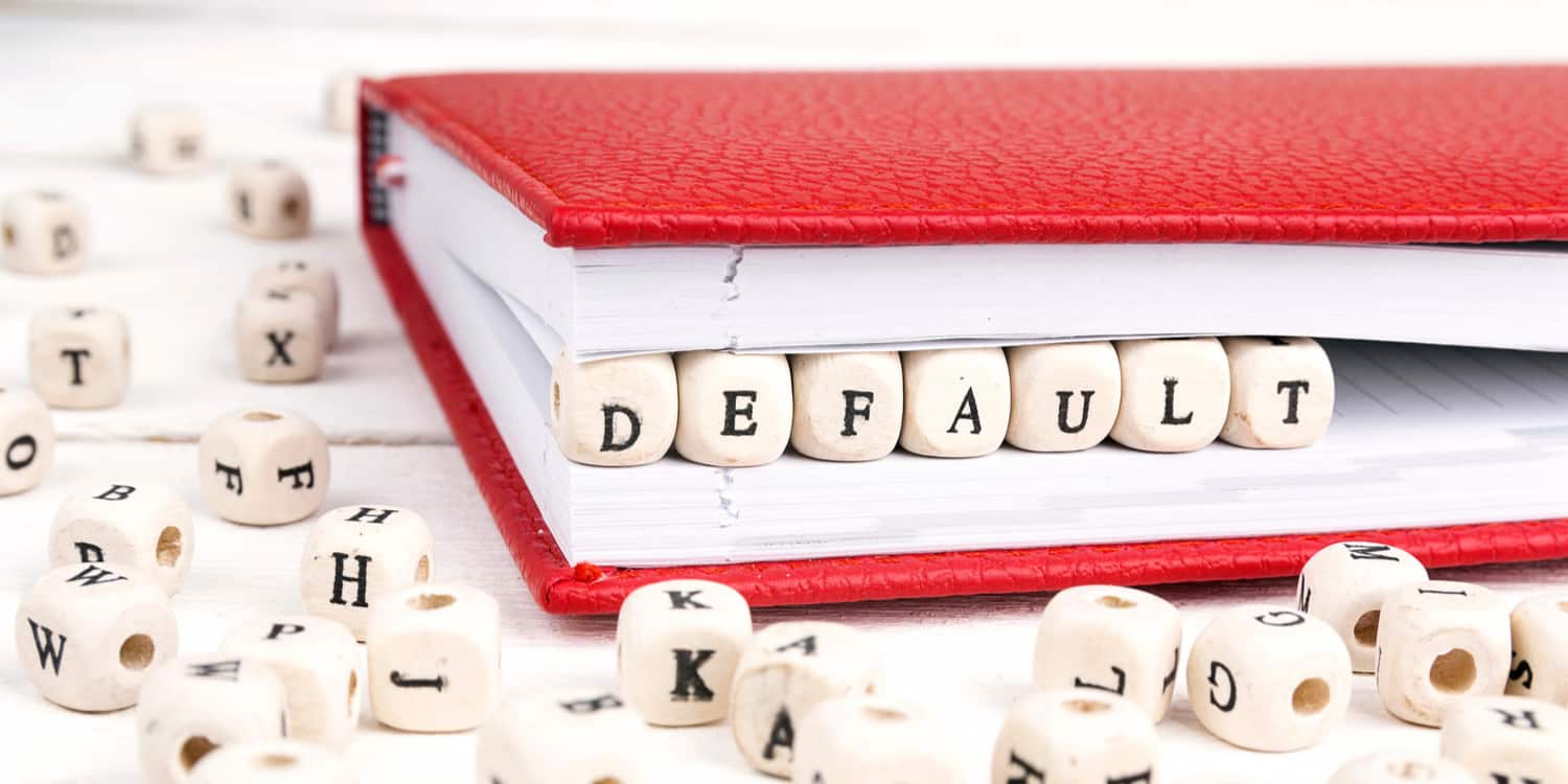 The word 'default' spelled out on a row of wooden blocks, set within the edge of a folded red notebook, illustrating that Model articles of association is the default set provided by Companies House.