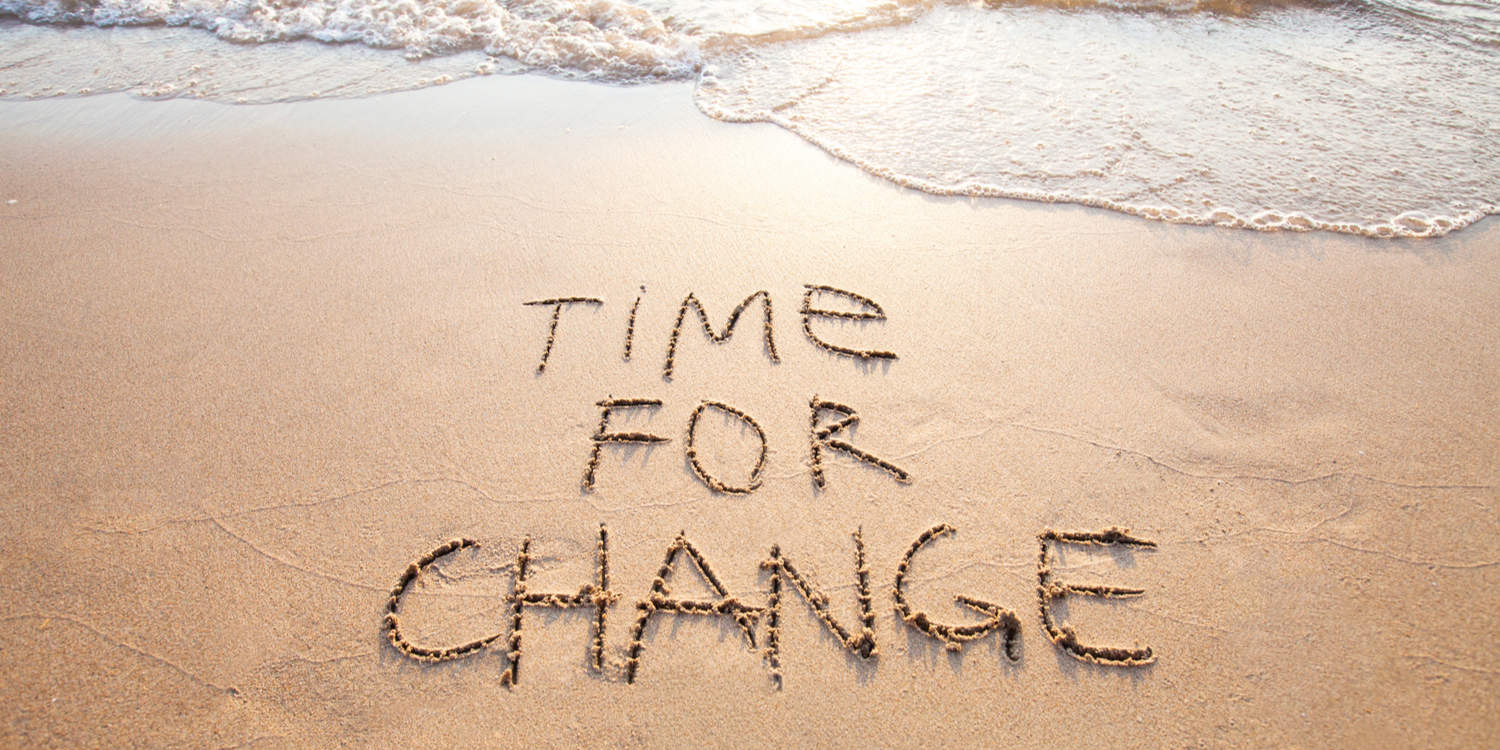 Photograph of a beach with the words 'Time for Change' written in the wet sand, representing the concept of changing your company name.