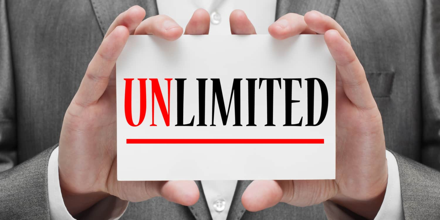 Photograph of a business person holding up a white card which displays the text 'UNLIMITED' in red and black print, representing the unlimited company structure.