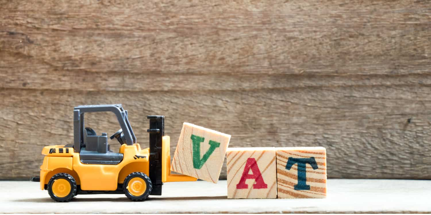 Image of toy forklift truck moving 3 wooden blocks each with the letters V, A and T displayed on them, depicting the concept of VAT registration.