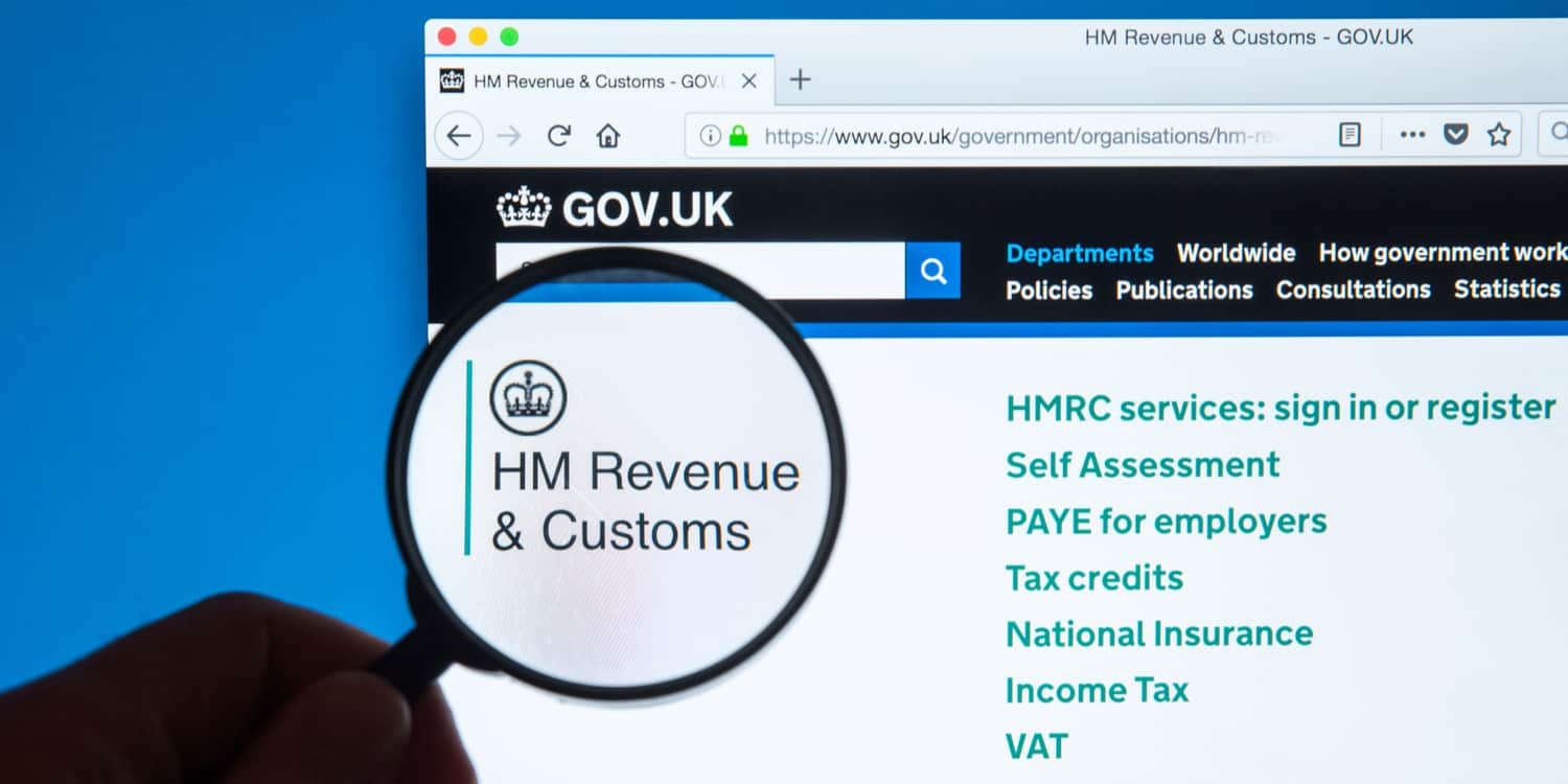 GOV.UK website with magnifying glass held over the heading 'HM Revenue & Customs' to add focus and make larger.