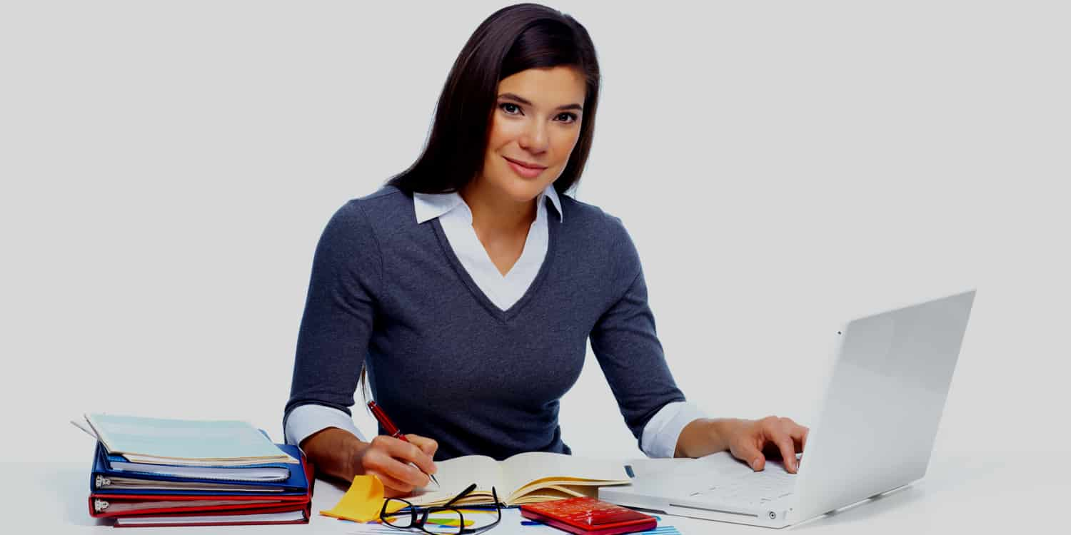 Business woman sitting at desk with laptop, calculator and paperwork preparing annual accounts.