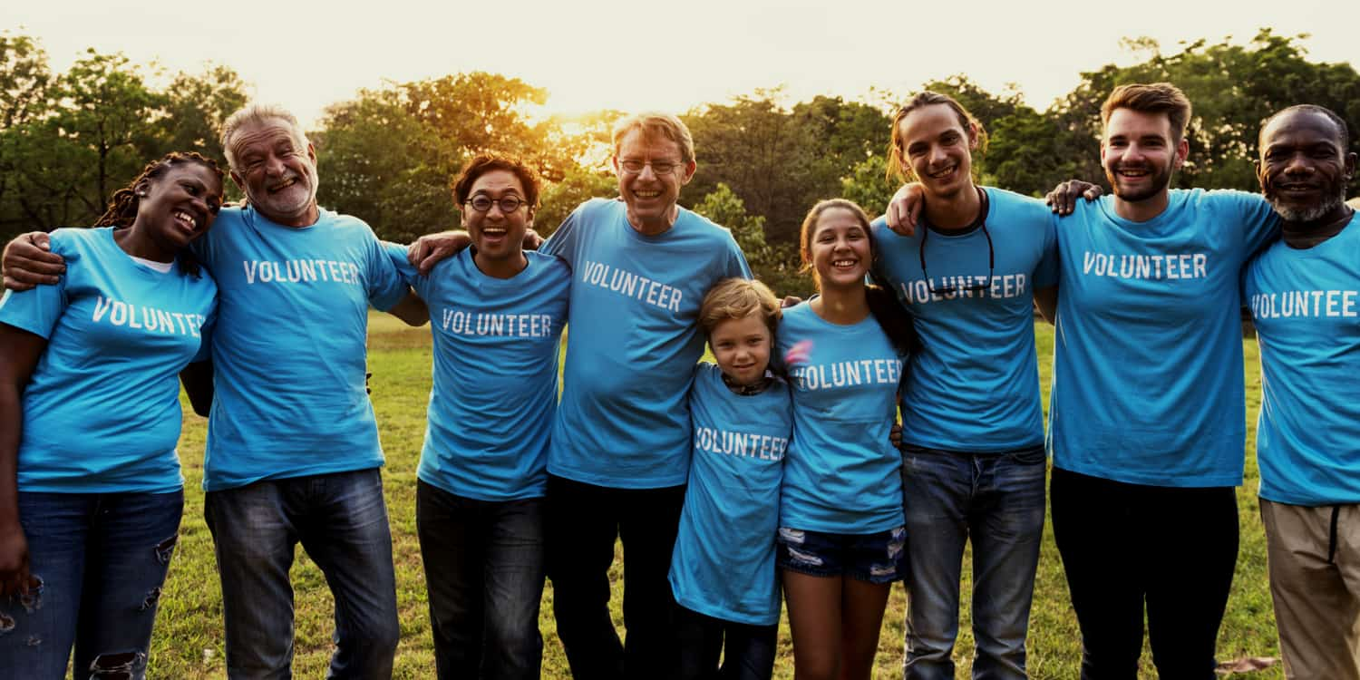 Group of charity workers laughing and embracing in field at sunrise, wearing t-shirts displaying the word 'VOLUNTEER'.