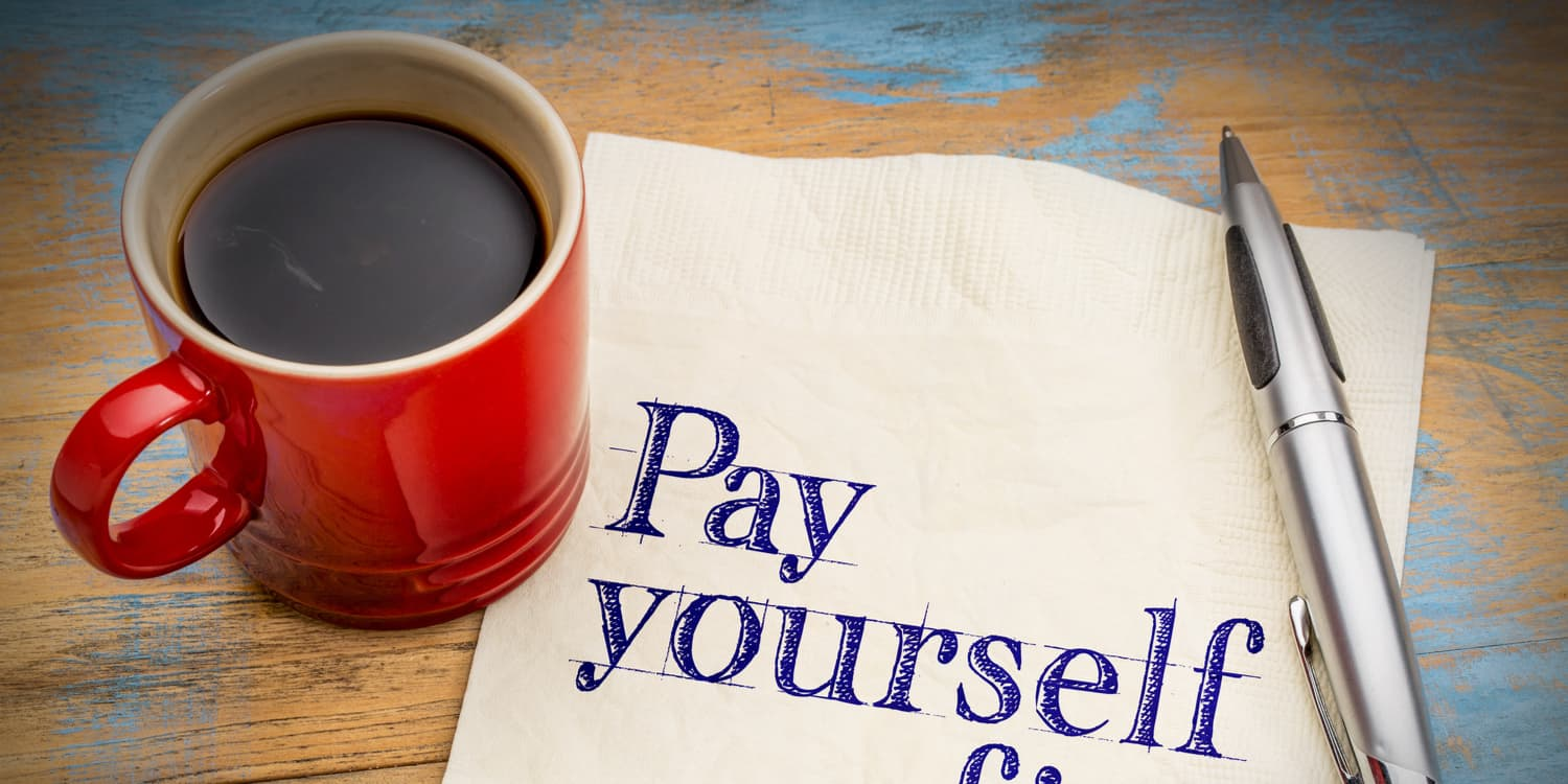 'Pay yourself' written on a napkin, with cup of coffee and pen also sitting on the table.