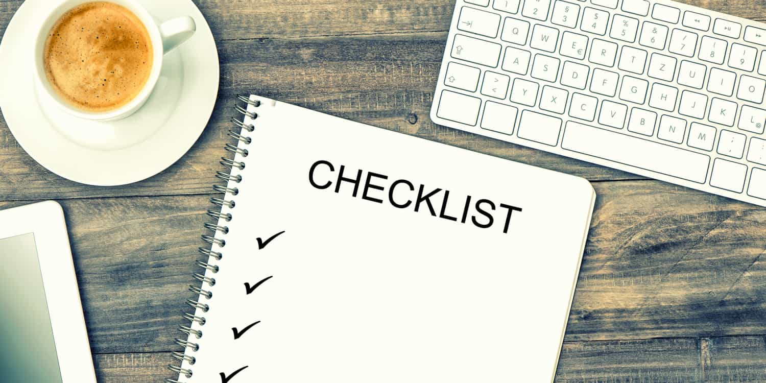 Notebook displaying the headline 'Checklist' with ticks, digital tablet pc, keyboard and coffee on wooden background.