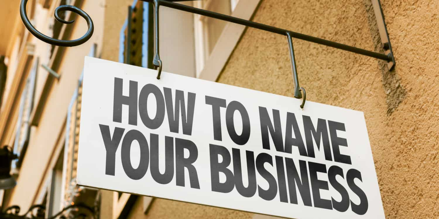 Sign hanging from wall bracket displaying the phrase 'HOW TO NAME YOUR BUSINESS'