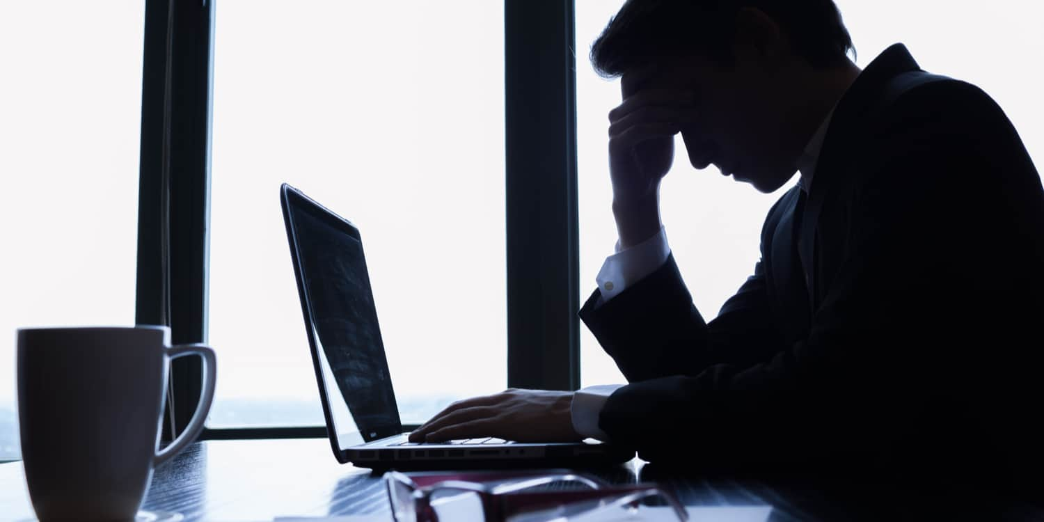 Worried businessman sitting at desk with laptop and hand holding forehead.
