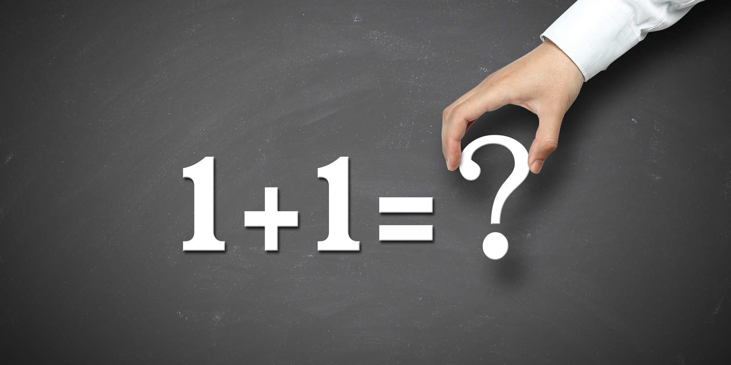 White magnetic numbers and symbols being placed on a blackboard displaying '1 + 1 = ?' illustrating the concept of whether 2 businesses can run under one company.