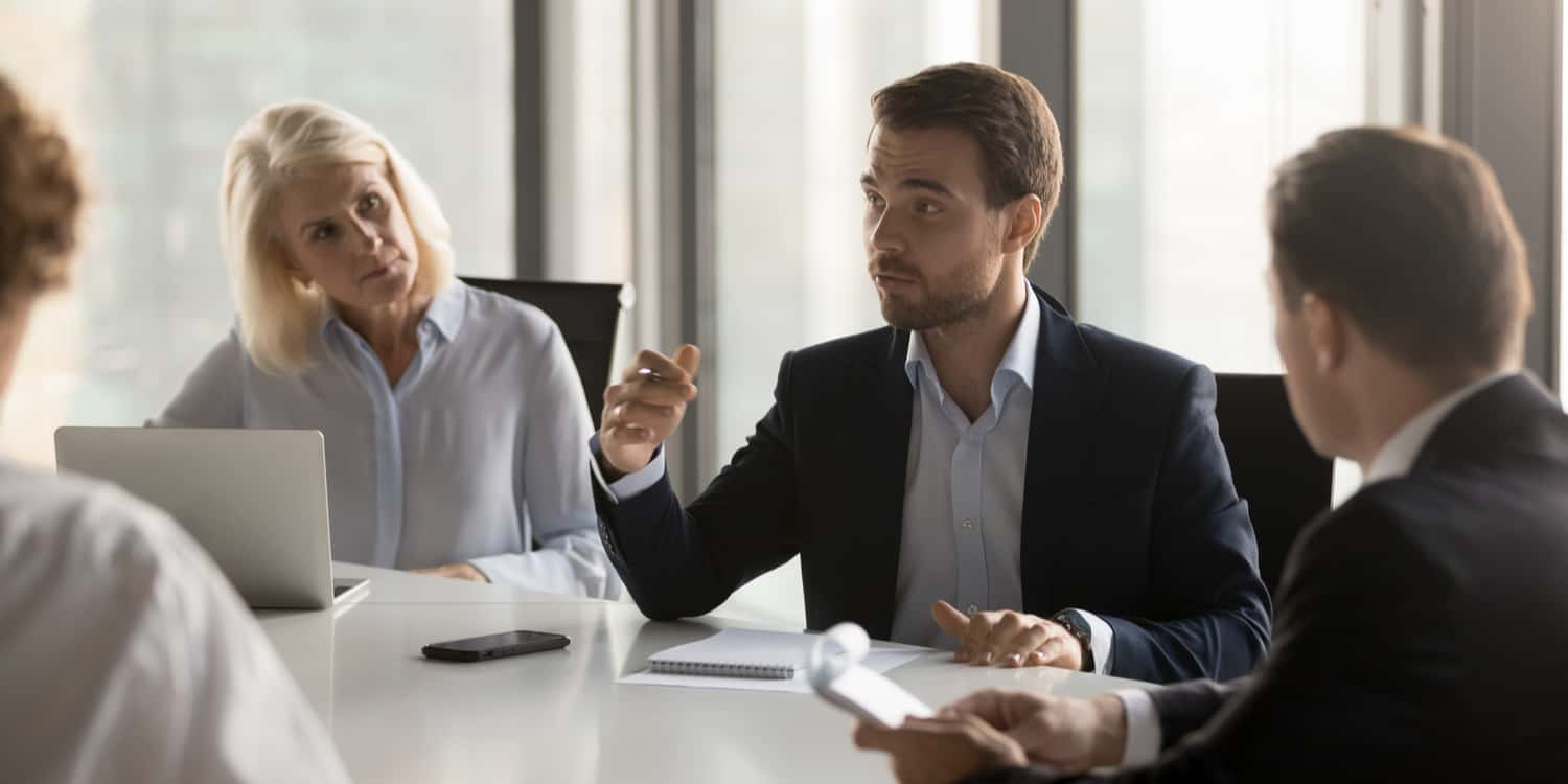Image of 4 individuals in a business meeting, representing the roles of company shareholders and directors.