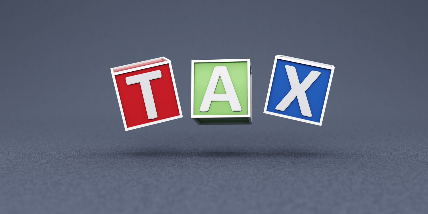 Three coloured cubes each with a letter in white font spelling the word TAX.