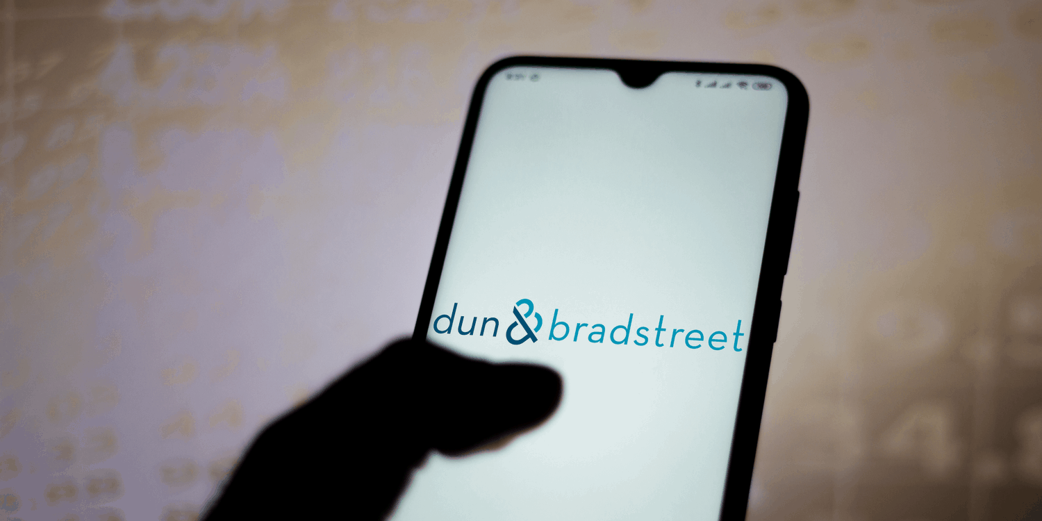 Mobile phone with business name 'dun & bradstreet' displayed on screen in blue text.