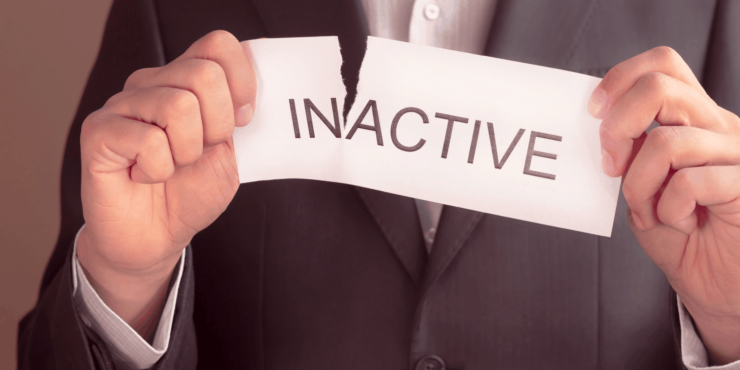 Businessman in dark grey suit tearing a piece of paper with the word INACTIVE printed on it in black font.