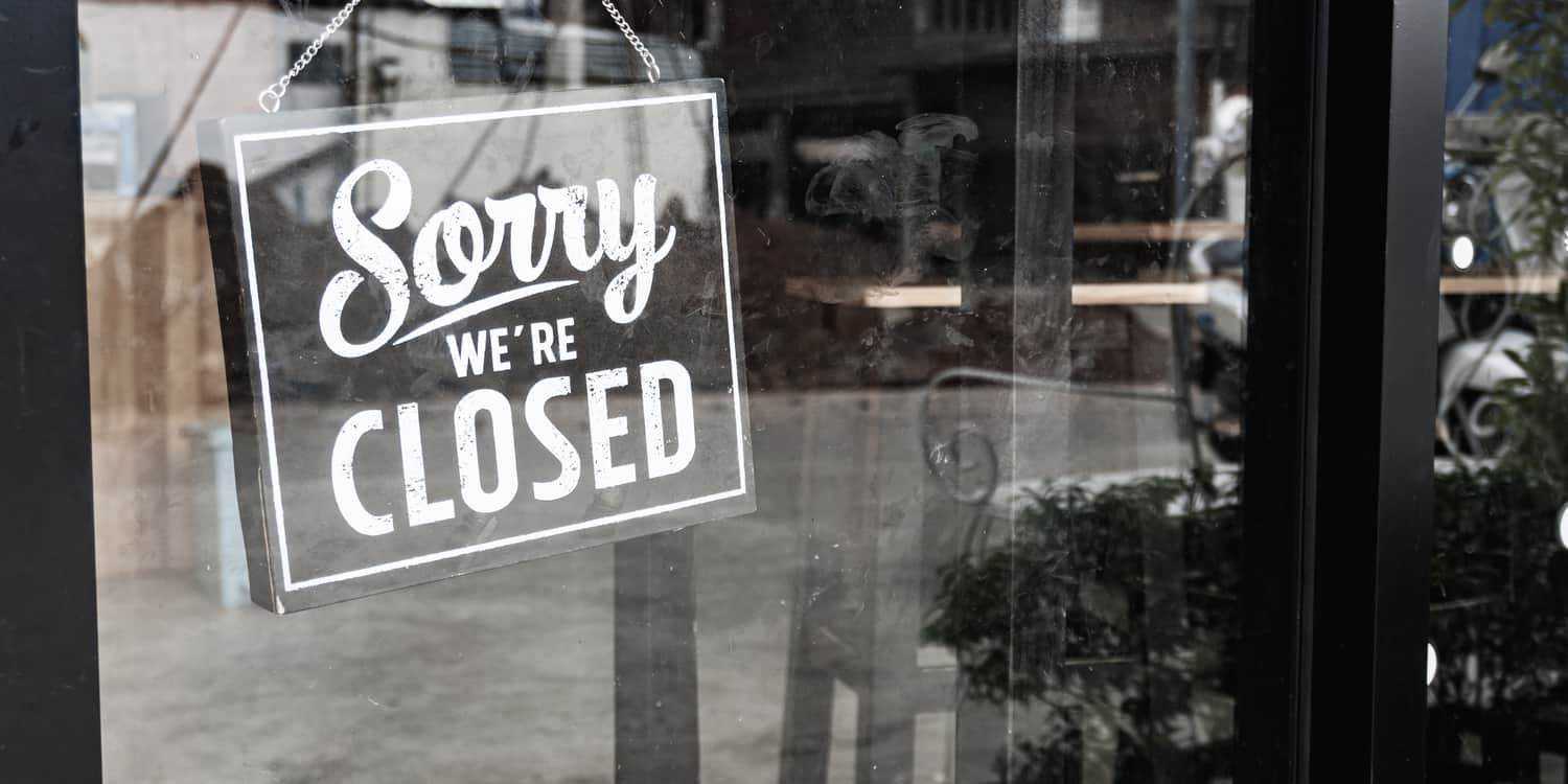 Black and white image of 'Sorry we're Closed' sign hanging in a shop window.