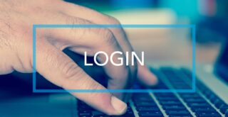 Male hand using a laptop keyboard with 'LOGIN' button overlaid with white text and blue border.